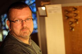Michael Georgi sitzt an der Orgel, das Licht ist angeschaltet, er trägt eine Brille und er schaut in die Kamera. - Copyright: Thomas Moll