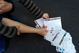 Eine Kinderhand und eine Erwachsenenhand ziehen eine Verlosungskarte aus einem am Boden liegenden Stapel - Copyright: Cornelia Schäfer