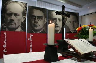Im Vordergrund ein Altar mit Kerzen, Kruzifix, aufgeschlagener Bibel und Blumenstrauß, im Hintergrund sieht man vier Stellwände mit großen Schwarz-Weiß-Porträts von Männern - Copyright: Ines Langhorst