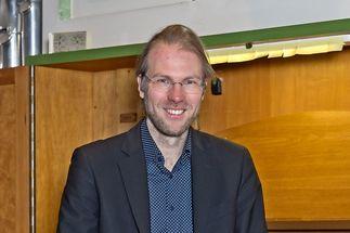 Junger Mann (Organist) sitzt mit dem Rücken zu einer Orgel und lächelt in die Kamera - Copyright: Ev.-Luth. Kirchengemeinde Schwarzenbek