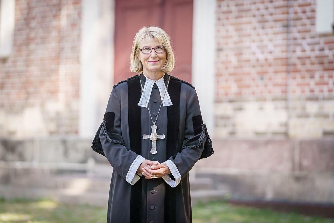 Pröpstin Frauke Eiben im Talar vor einer Backsteinkirche - Copyright: Guido Kollmeier
