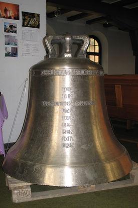 """eine im Kirchenraum stehende Glocke mit Inschrift: """"Ich bin die Auferstehung und das Leben"""" - Copyright: Ev.-Luth. Kirchenkreis Lübeck-Lauenburg"""