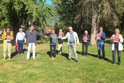 Neun Menschen halten Plakate in der Hand. Im Hintergrund eine Wiese mit hohen Bäumen. - Copyright: privat