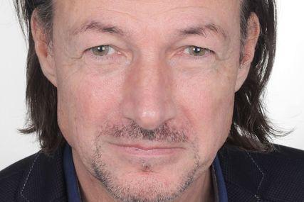 Ein Mann mit dunklen, halblangen Haaren und einem gepflegten Dreitagebart schaut ernst in die Kamera. - Copyright: Rüdiger Schmidt