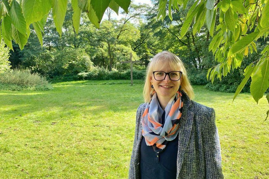 Frau steht lächelt unter einem Baum auf einer Wiese. - Copyright: Bastian Modrow