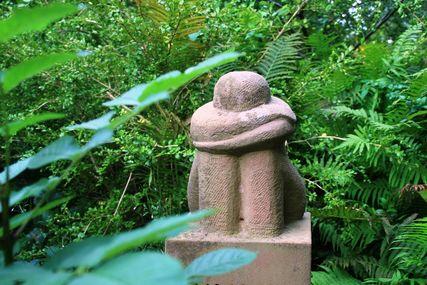 Eine Skulptur aus Stein. Sie zeigt einen Menschen, sitzend mit angezogenen Knien, verschränkten Armen und gesenktem Kopf.  - Copyright: Kirchenkreis Lübeck-Lauenburg