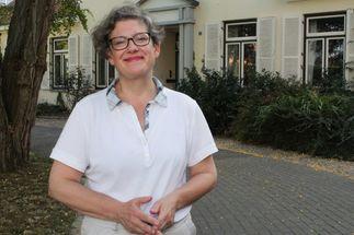 Eine Frau mit Brille. Sie trägt ein weißes Polo-Shirt. Im Hintergrund ein Haus. - Copyright: Oliver Pries