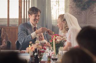 Ein Brautpaar prostet sich lachend mit Schnapsgläsern zu. Der Bräutigam hält einen Säugling auf dem Schoß. - Copyright: Maipo Film