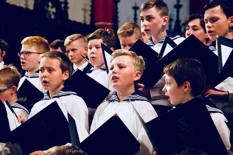 Thüringer Sängerknaben bei einem Konzert stehen als Chor hinter- und nebeneinander, wie die Orgelpfeifen und singen. In ihren Händen halten Sie Liedermappen.
