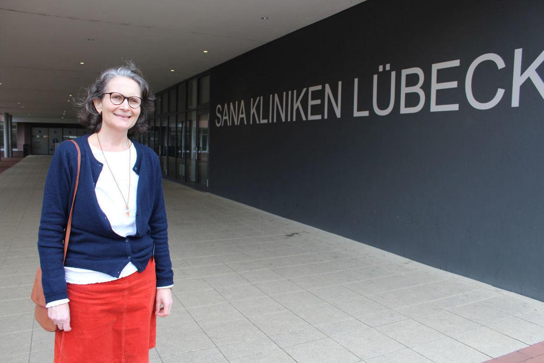 Links steht Frau Grossmann mit weißem Oberteil, blauer Stickjacke und rotem Rock, rechts ist der Schriftzug Sana Kliniken Lübeck in Großbuchstaben und weißer Schrift auf dunkelgrauer Wand zu sehen - Copyright: Christine Grossmann