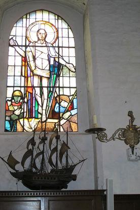 Blick auf ein Kirchenfenster und ein darunter stehendes Segelschiff-Modell - Copyright: Ev.-Luth. Kirchenkreis Lübeck-Lauenburg