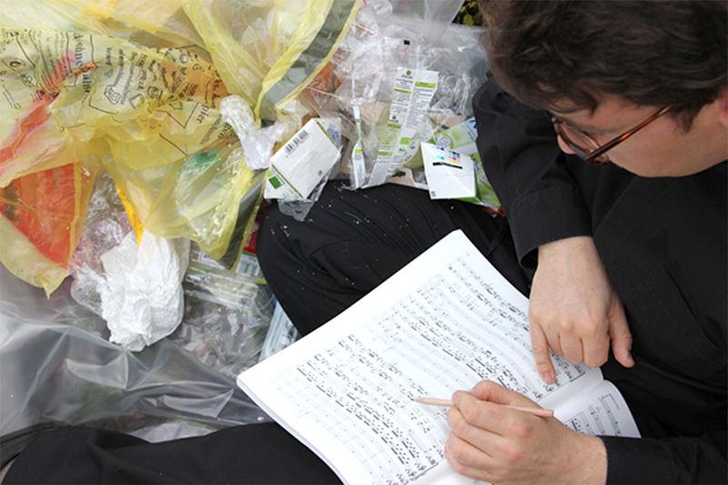 Mit einem Konzert im Müll wollen Musizierende in der St.-Nicolai-Kirche Mölln auf den Klimawandel aufmerksam machen. Auf dem Foto ist ein Musiker mit Noten und Plastikmüll zu sehen.