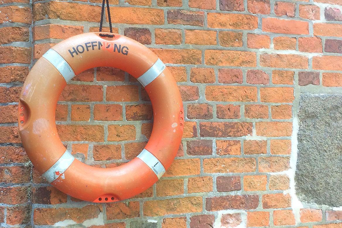 Ein älterer oranger Rettungsring mit Nutzungsspuren hängt an einer Backsteinwand. - Copyright: Ev.-Luth. Kirchenkreis Lübeck-Lauenburg