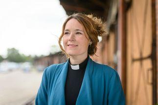 Eine Pastorin mit blauer Jacke und hochgestecktem braunen Haar am Hafenschuppen von Lübeck - Copyright: Guido Kollmeier