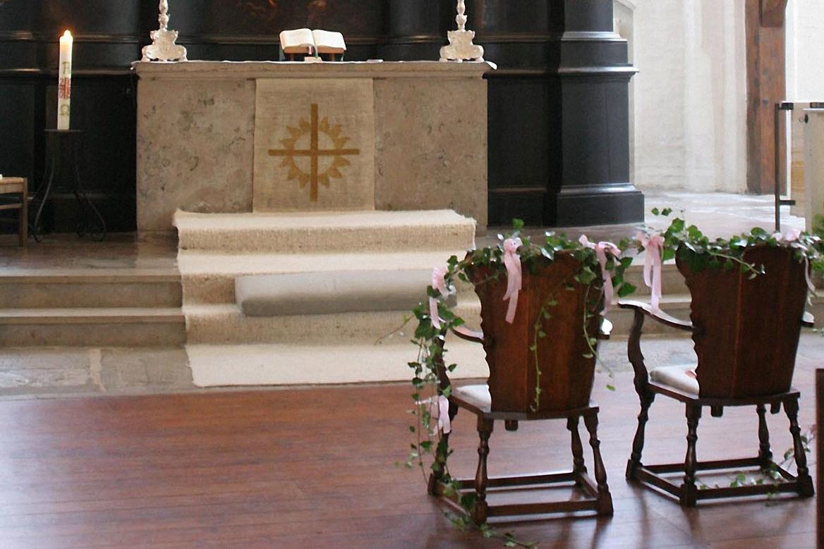 geschmückte Holzstühle in der Kirche vor dem Altar - Copyright: Ev.-Luth. Kirchenkreis Lübeck-Lauenburg