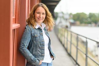 Eine Frau schaut lächeln in die Kamera. Sie lehnt an einer roten Holzwand. - Copyright: Guido Kollmeier