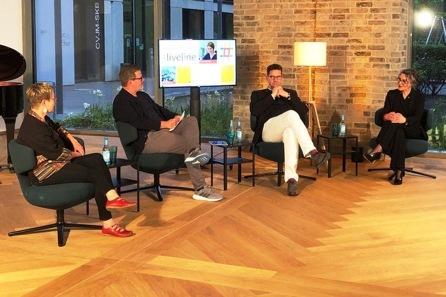 Vier Menschen sitzen auf Sesseln in einem Raum mit Holzboden und großen Fensterflächen. Ein Bildschirm, eine Stehlampen und Beistelltische sind zu sehen. - Copyright: Ines Langhorst