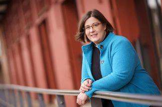 Eine Pastorin mit blauer Jacke, die am Geländer aufgestützt in die Kamera schaut.  - Copyright: Guido Kollmeier