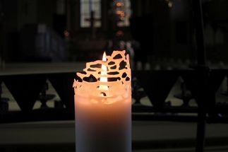 Eine brennende weiße Kerze in einer dunklen Kirche.  - Copyright: Ev.-Luth. Kirchenkreis Lübeck-Lauenburg