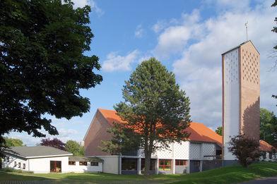 Außenansicht der Auferstehungskirche mit umliegenden Bäumen und Wiese - Copyright: Manfred Maronde