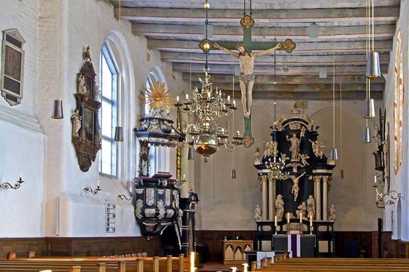 Der Innenraum einer Kirche mit Bänken, einer Kanzel und einem Altar. Ein Kreuz hängt im Raum.
