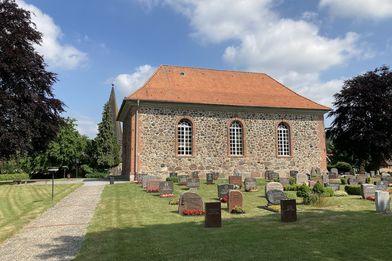 Die St. Andreas Kirche Sahms, darüber blauer Himmel, davor ein Teil des Friedhofs - Copyright: Stefan Wilmer