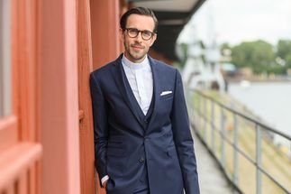 Pastor Jonathan Ide lehnt im dunklen Anzug und weißem Hemd an der Wand. - Copyright: Guido Kollmeier
