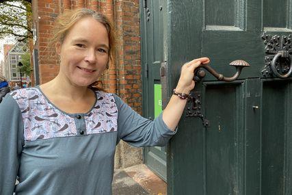 Frau steht an einer Kirchentür und öffnet diese - Copyright: Bastian Modrow