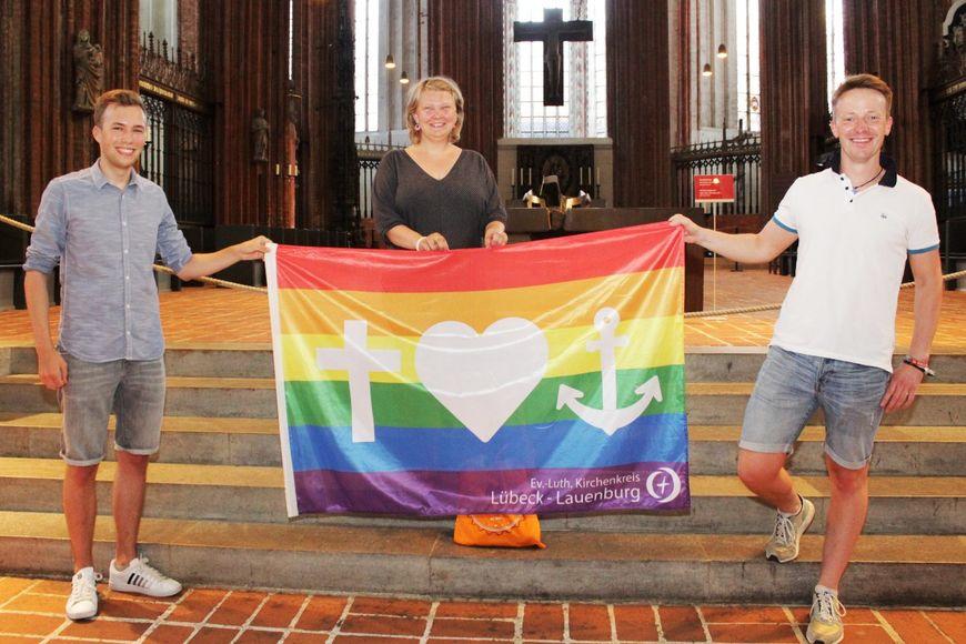 Drei Menschen halten eine Regenbogenflagge mit den Symbolen Kreuz, Herz und Anker. Im Hintergrund der Altarraum der Lübecker Marienkirche. - Copyright: Oliver Pries