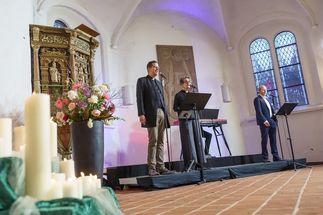 Blick in den Kirchraum der Lübecker St. Jürgen-Kapelle, Links im Vordergrund Kerzen. Im hinteren Teil eine kleine Bühne, drei Sänger:innen. - Copyright: Guido Kollmeier
