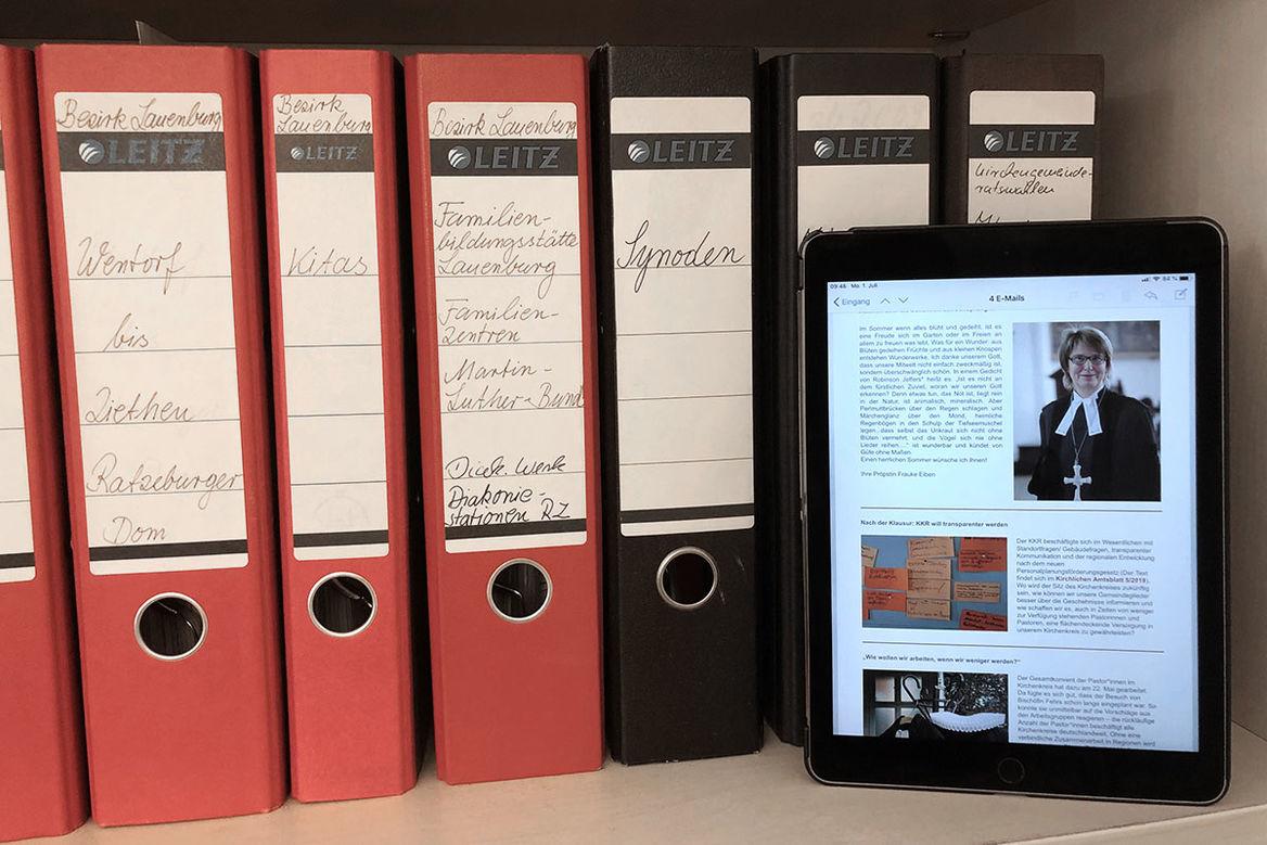"""Ein iPad steht vor mehreren schwarzen und roten Aktenordner und zeigt Ausschnitte aus dem Newsletter """"Kirchenkreis informiert"""" - Copyright: Ev.-Luth. Kirchenkreis Lübeck-Lauenburg"""