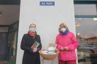 Zwei Frauen stehen vor einer grauen Wand. Zwischen ihnen steht ein kleiner Korb auf einem Ständer, in dem gerollte Papiere und blaue Flyer liegen. Über ihnen steht auf einem Straßenschild: 'Markt' - Copyright: Carola Scherf