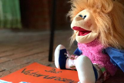 Eine Handpuppe mit langen Haaren, sitzt recht in der Ecke auf einem roten Pappschild, auf welchem 'Das Vaterunser' steht - Copyright: Ev.-Luth. Kirchenkreis Lübeck-Lauenburg