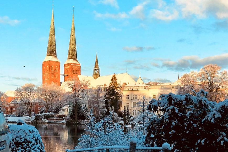 Blauer Himmel, der Dom zu Lübeck, davor der Mühlenteich. Alles ist schneebedeckt. - Copyright: Ines Langhorst