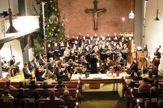 Blick von der Empore in eine Kirche auf den Altar. Ein Chor und Instrumentalisten, in den Bänken sitzen Menschen. - Copyright: KG Kücknitz