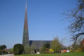 Außenansicht der Paul-Gerhardt-Kirche mit umliegenden Bäumen und Wiese - Copyright: Ev.-Luth. Kirchenkreis Lübeck-Lauenburg
