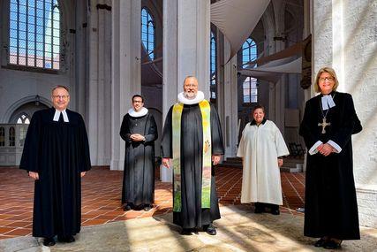 Fünf Pastor:innen, im Hintergrund der Innenraum der Lübecker Petrikirche. - Copyright: Bastian Modrow