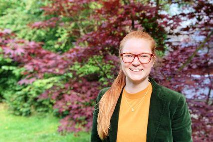 Eine Frau mit langen Haaren, Brille, grüner Jaclke und orangenem Oberteil schaut in die Kamera. Im Hintergrund eine Hecke mit grünen und roten Blättern - Copyright: Foto: privat