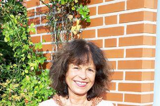 Kirsten Steinbeck steht vor einer teils grün bewachsenen Ziegelmauer. Sie hat schulterlanges krauses dunkles Haar. Sie trägt ein helles Oberteil und lächelt in die Kamera. - Copyright: Kirsten Steinbek