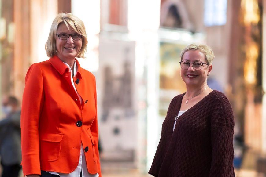 Zwei Frauen im Halbportrait schauen freundlich in die Kamera. Sie sind einander zugewandt, im Hintergrund ist unscharf der Kirchraum von St. Marien zu erkennen. - Copyright: Felix König /Agentur 54°