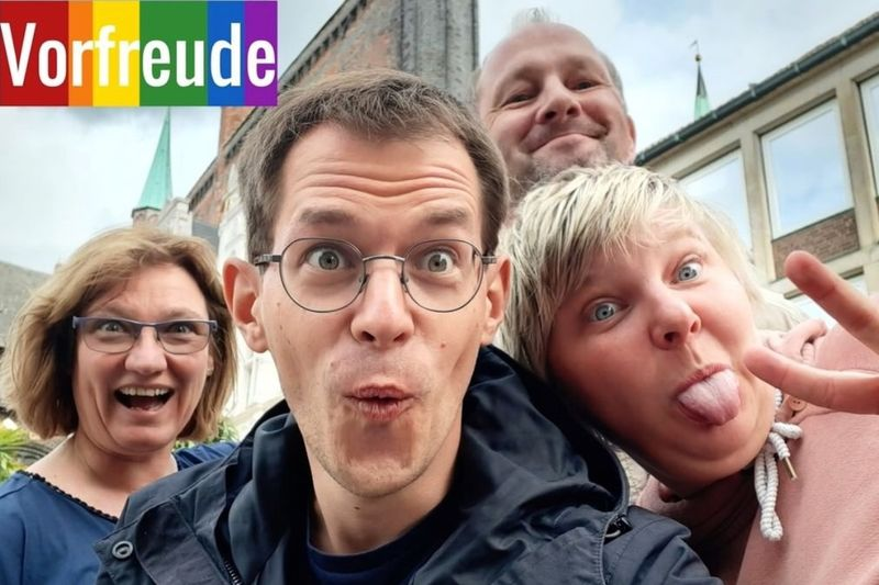 Ein Selfie: Vier Menschen schauen lachend in die Kamera.