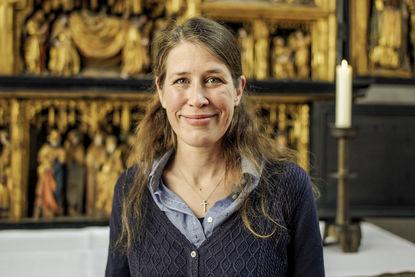 Pastorin Inga Meißner steht vor dem Altar. Auf dem Tisch hinter hier steht rechts eine Kerze. Frau Meißner hat lange braune Haare. Sie schaut in die Kamera. - Copyright: Thorsten Wulff