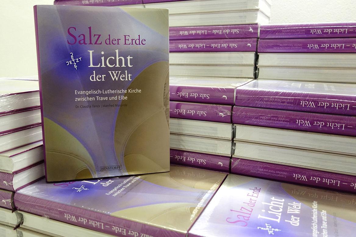 """Buchband """"Salz der Erde – Licht der Welt"""": Mehrere übereinandergestapelte Bücher dieses Buchbandes. Ein Buch steht aufrecht mit dem Buchdeckel nach vorne"""