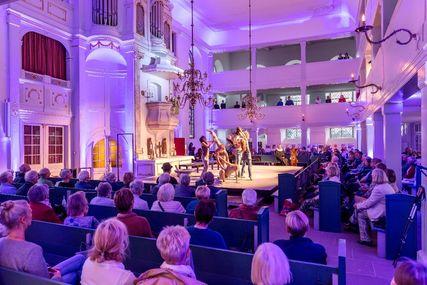 Ein Kirchraum. Vor dem Altar eine Bühne. Menschen sitzen in Reihen rund um die Bühne. Auf der Bühne Ballett. - Copyright: Dirk Eisermann