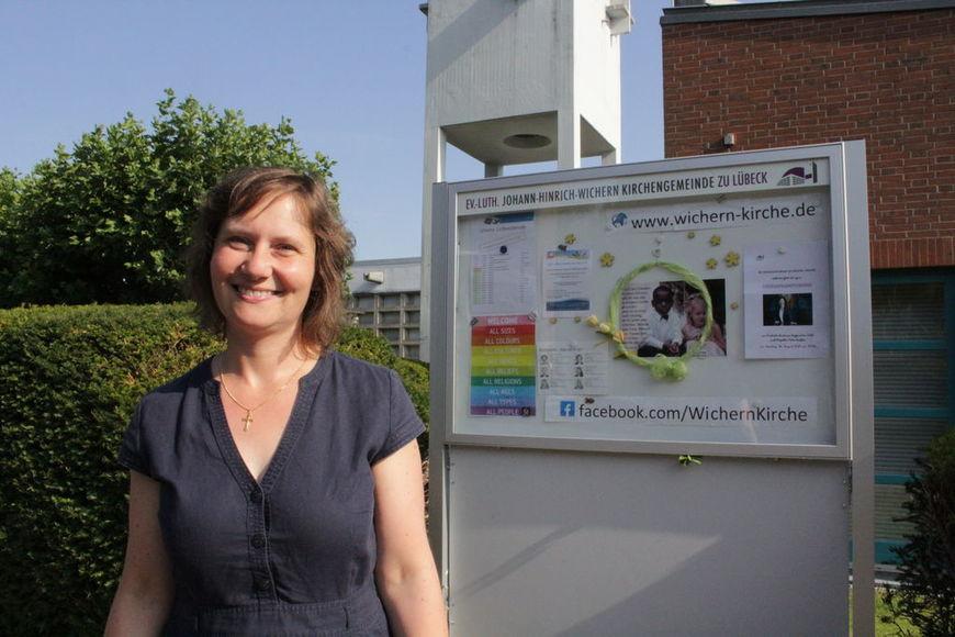 Eine Frau im Portait unter freiem Himmel. Im Hintergrund eine Hecke, ein Gebäude und der Schaukasten mit Plakaten. - Copyright: Oliver Pries
