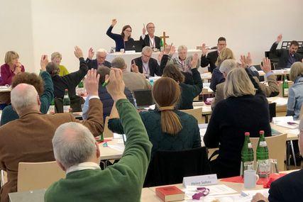 Menschen in einem Raum, sitzend, heben einen Arm zur Abstimmung. - Copyright: Kirchenkreis Lübeck-Lauenburg