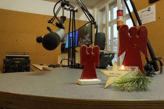 Im Vordergrund sieht man zwei stilisierte rote Engel hinter einer brennenden Kerze mit einem Tannenzweig und einem Stern. Im Hintergrund sieht man ein Radiostudio. - Copyright: Georg Gemander