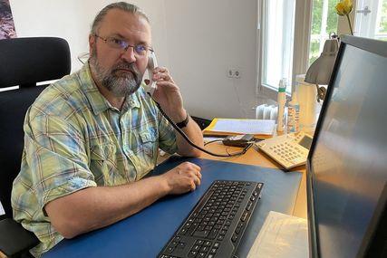 Mann in kariertem Hemd sitzt am Schreibtisch und telefoniert. - Copyright: Bastian Modrow