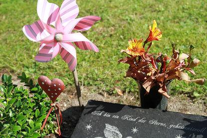 Grabstein mit der Aufschrift: 'Ich bin ein Kind der Sterne, geheimnisvoll', neben dem eine rosa Windmühle und ein kleines rotes Herz mit weißen Punkten steckt. Eine Blumenvase mit Blumen steht am Kopfende des Grabsteins.