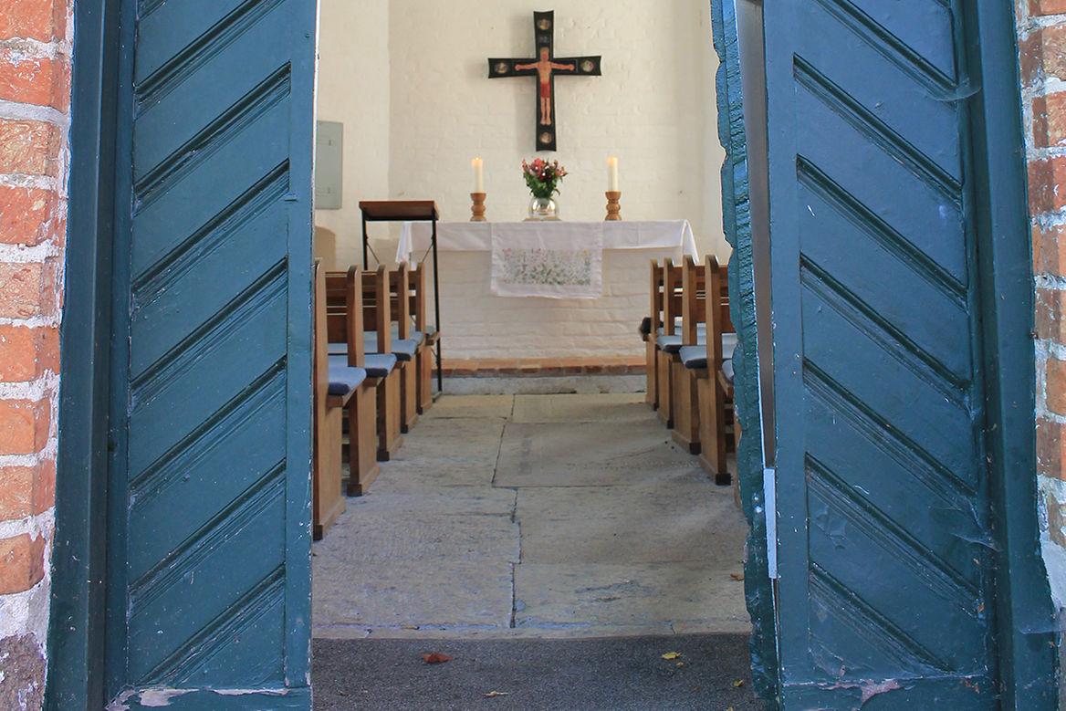 Eine offene blaue Kirchentür gibt den Blick frei zu einem Kirchenaltar auf dem zwei große, weiße, brennende Kerzen zu sehen sind. Zwischen den Kerzen steht eine runde Glasvase mit Blumen, darüber hängt ein Altarkreuz. Im vordergrund sind braune Holz-Kirchenbänke mit blauen Sitzauflagen zu sehen.